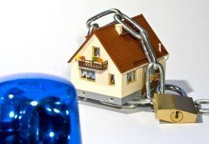 Haus mit einer Kette gesichert und einem Blaulicht im Vordergrund